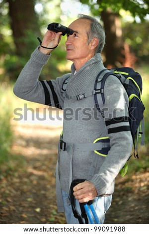 Hiker looking through binoculars - stock photo
