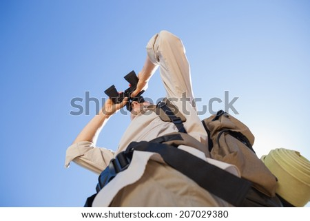 Hiker looking through binoculars on country trail on a sunny day - stock photo