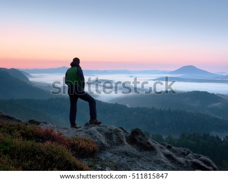 Hiker  man on rock watch over valley and foggy morning landscape. Beautiful fall morning. Autumn hilly cvountryside