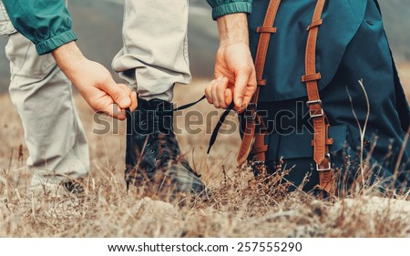 Hiker man tying shoelaces on nature outdoor, near backpack. View of legs. Hiking and leisure theme