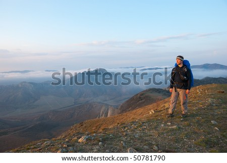 Hiker on a peak enjoys mountain landscape