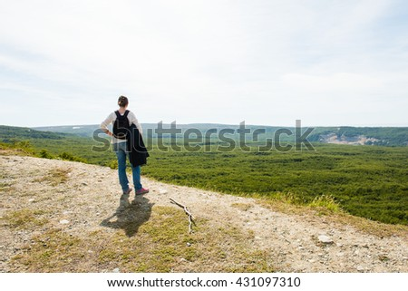 Hiker on a rocky outcrop enjoying a mountain view