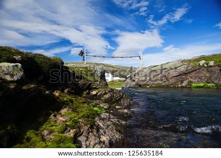 Hiker on a Summer bridge in the Hardangervidda Nationalpark in Norway - stock photo