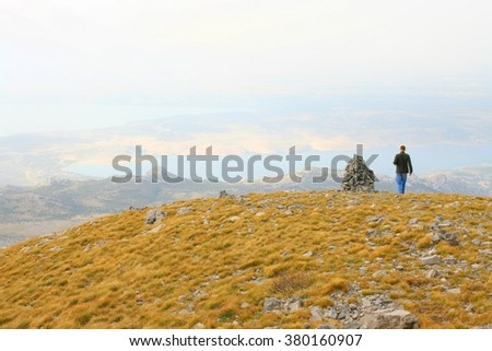 Hiker on mountain peak with sea coast in background