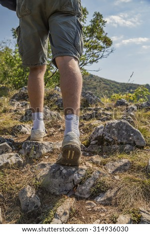 Hiker on mountain rocks walking.  Made with selective focus and shallow depth of field.