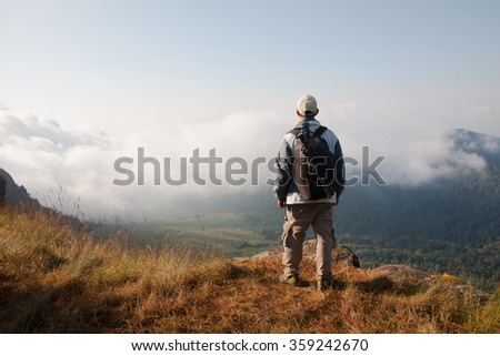 Hiker on mountain with backpack, adventure travel concept - stock photo