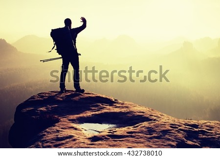 Hiker on peak. Backpacker with poles in hand shadowing eyes. Sunny spring daybreak in rocky mountains. Hiker on rocky view point above misty valley.