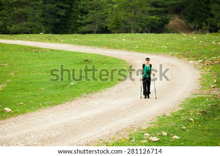 Hiker on road in forest - stock photo