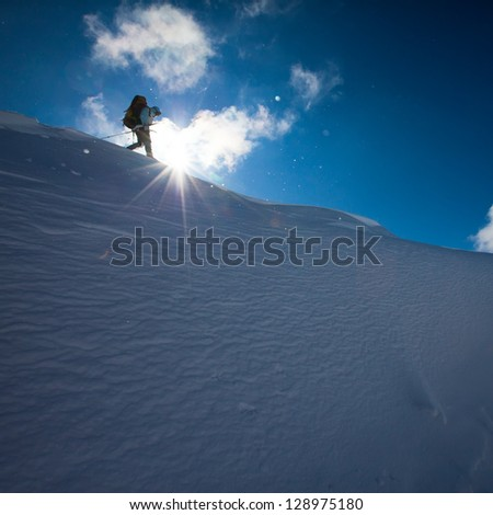 Hiker on the edge of the mountain in winter time - stock photo