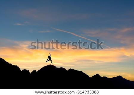 hiker on the peak at sunset - stock photo