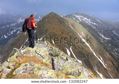 Hiker on top of the mountain admiring the amazing view in spring time