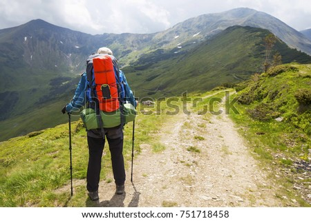 Hiker outdoor with equipment on mountain path, nature mountain exploring, hiking and trekking