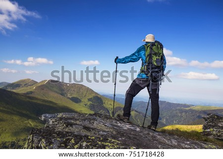 Hiker outdoor with equipment on mountain rock, nature mountain exploring, hiking and trekking