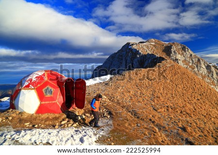 Hiker outside red refuge on top of the mountain  - stock photo