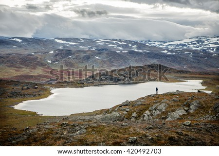 Hiker over a lake in the autumn wilderness of Sweden
