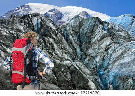Hiker overlooking the huge crevasses and rugged terrain of the the glacier he's about to climb, absorbing the sheer challenge he's facing - stock photo