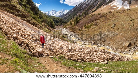 hiker passes through an avalanche in the mountains of Central Caucasus