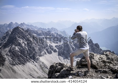 Hiker photographing on the summit of the Allgau Alps - stock photo