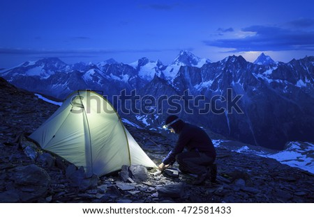 Hiker pitching his tent during an evening in the Swiss mountains.
