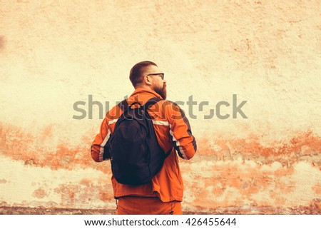 Hiker portrait. Explorer talking via radio station. Young man tourist with a backpack sitting on top of a mountain, sunglasses, beard and mustache - stock photo