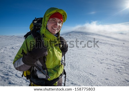 Hiker posing at camera in winter mountains