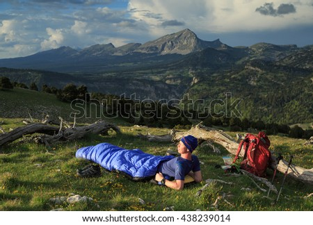 Hiker preparing for a bivouac in his sleeping bag between two dead trees in the Vercors mountains, France.