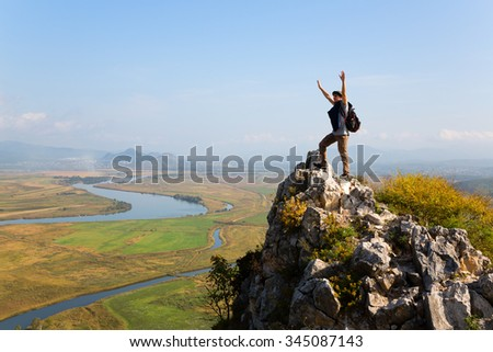 Hiker raises his arms up and screaming with delight. Autumn day.