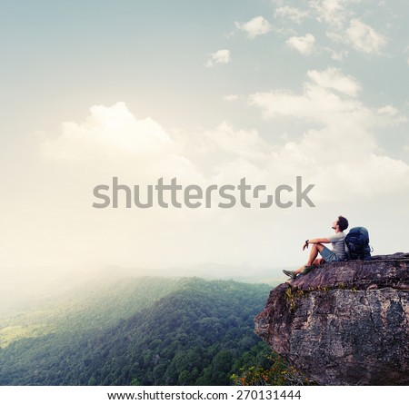 Hiker relaxing on the rock - stock photo