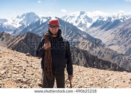 Hiker relaxing on top of a mountain and enjoying valley view. Tien Shan mountains, central asia, Kyrgyzstan.
