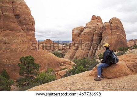 Hiker resting on a trail at Arches National Park in Moab Utah