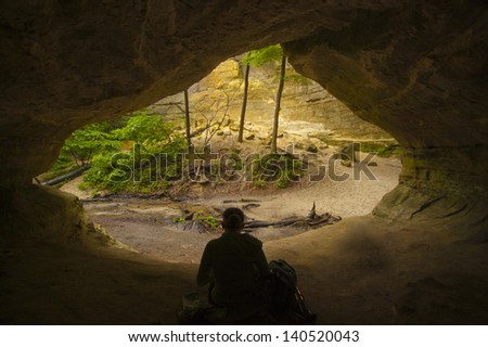 Hiker rests in natural cave