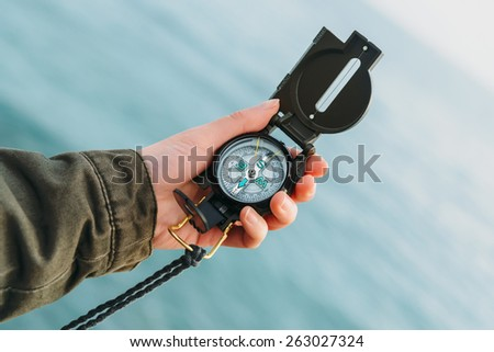 Hiker searching direction with a compass on background of sea. Point of view shot