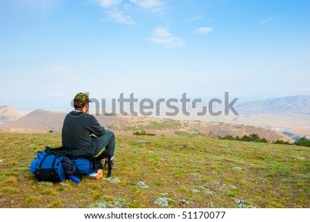 Hiker sits on the slope and enjoy the scenery