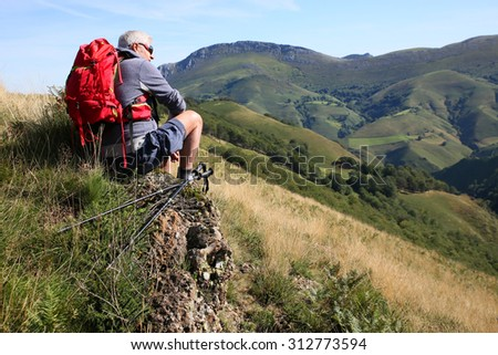Hiker sitting on a rock admiring Basque Country scenery