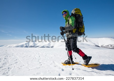 Hiker snowshoeing in winter mountains during sunny day - stock photo
