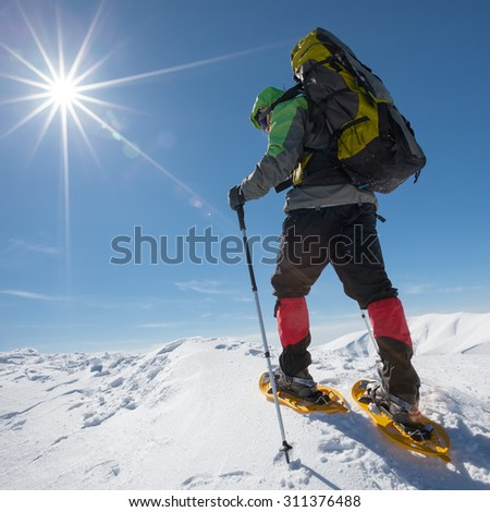 Hiker snowshoeing in winter mountains during sunny day