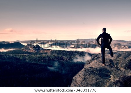Hiker stand on cliff of sandstone empires park and watching over the misty and foggy morning valley to Sun