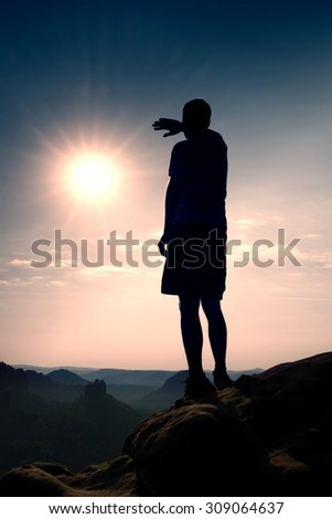 Hiker stand on the sharp cliff of sandstone rock empire and watch over the  morning valley to hot Sun.