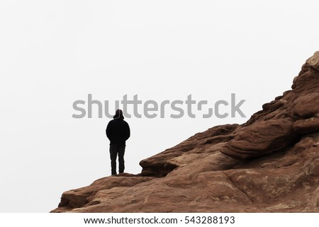 Hiker Standing Alone on Rocky Sandstone Cliffs at Arches National Park