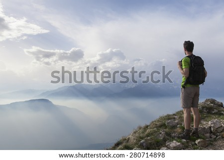 Hiker standing and enjoying incredible view of mountains - stock photo