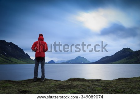 Hiker standing at lake Alftavath on the Laugavegur trail on Iceland. - stock photo