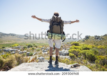 Hiker standing at the summit with arms outstretched on a sunny day