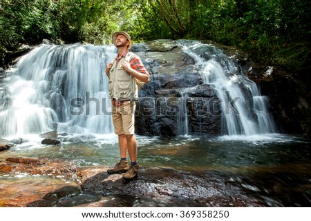 Hiker standing in front of a waterfall deep in the jungle - Sri Lanka - stock photo