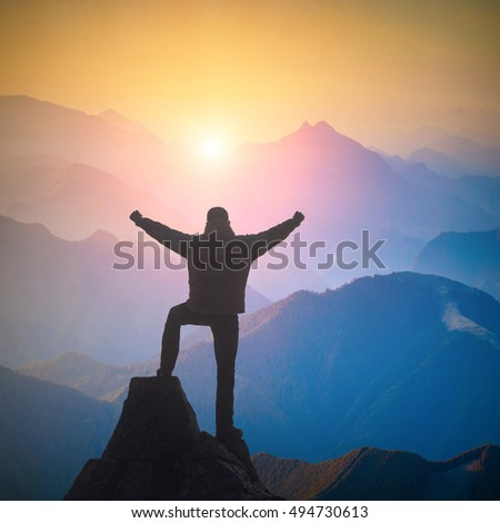 Hiker standing on a cliffs edge with raised hands and rejoices sunrise in a mountain valley.
