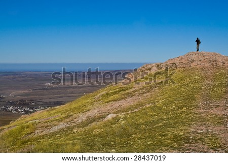 Hiker standing on mountain summit in sunny weather