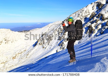 Hiker standing on the snowy mountain and taking pictures of the landscape