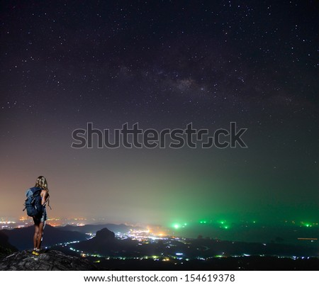 Hiker standing on top of a mountain and enjoying night sky view with a lots of stars and artificial city lights - stock photo