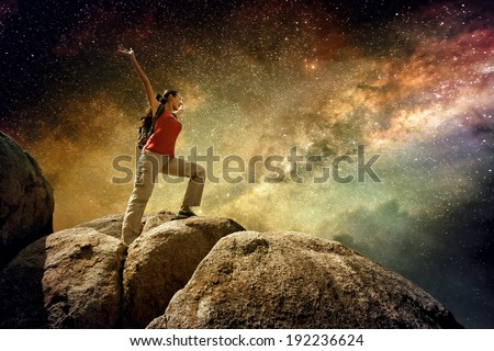 Hiker standing on top of a mountain and enjoying night sky view with a lots of stars. Picture of a series of Adventure and Travel. - stock photo
