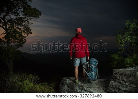 Hiker standing on top of the mountain and enjoying twilight valley view - stock photo