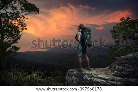 Hiker standing on top of the mountain and watching sunset over the valley - stock photo